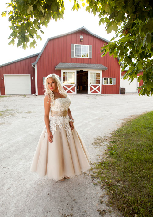 Alysa Hutton wearing Justin Alexander 8465 in front of Rustic Manor 1848